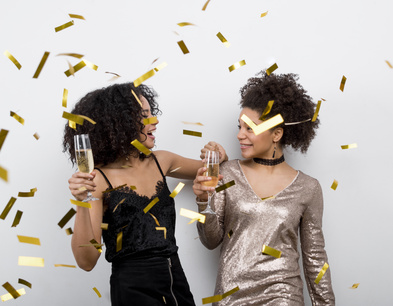 Female friends have fun with confetti and champagne